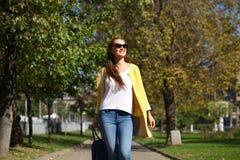 Happy woman in yellow coat walking autumn street Royalty Free Stock Photos