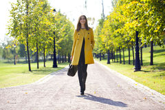 Happy woman in yellow coat walking autumn street Stock Photo