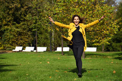 Happy woman in yellow coat walking autumn street Royalty Free Stock Image