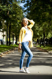 Happy woman in yellow coat walking autumn street Stock Photography