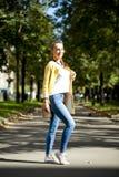 Happy woman in yellow coat walking autumn street Stock Images
