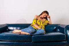 A happy woman in a yellow dress sitting on a sofa. A beautiful happy young woman in a yellow dress sitting on a sofa stock photos