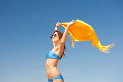 Happy woman with yellow sarong on the beach Stock Image