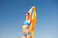 Happy woman with yellow sarong on the beach Royalty Free Stock Images