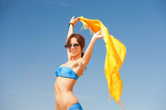 Happy woman with yellow sarong on the beach Stock Photo