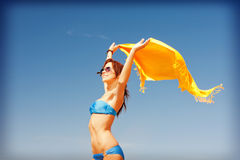 Happy woman with yellow sarong on the beach Stock Photography