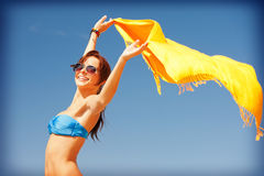 Happy woman with yellow sarong on the beach Stock Images