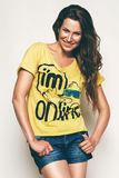 Happy woman in yellow t shirt. In studio Royalty Free Stock Photo