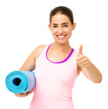Happy Woman With Yoga Mat Gesturing Thumbs Up. Portrait of happy young woman with yoga mat gesturing thumbs up over white background. Horizontal shot Royalty Free Stock Photo