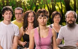 Happy woman in yoga meditation class. Portrait young women in yoga meditation class with group of people outdoors Stock Images