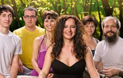 Happy woman in yoga meditation class. Portrait young women in yoga meditation class with group of people outdoors Stock Image