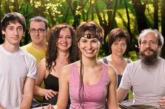Happy woman in yoga meditation class. Portrait young women in yoga meditation class with group of people outdoors Royalty Free Stock Photography