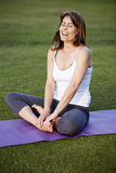 Happy woman in yoga position. Happy young woman on mat on grass in cross legged yoga position stock photos