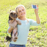 Happy woman and yorkshire terrier dog having fun takes selfie Royalty Free Stock Photos