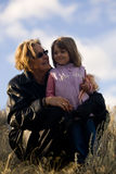 Happy woman with young girl in sun. Happy mature woman with young girl outside under blue sky Stock Images