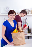 Happy woman and young man unpacking groceries Royalty Free Stock Photo