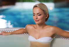 Happy womani sitting in jacuzzi at poolside Stock Image