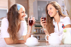 Happy women. With glasses of red wine talk about on kitchen royalty free stock images
