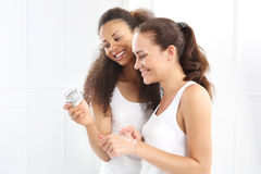 Happy women analyzes the composition of the cream. Royalty Free Stock Image