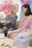 Happy Women At A Baby Shower. Surprised pregnant women with friend holding gift at a baby shower royalty free stock photography