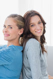 Happy women back against back and looking at camera Royalty Free Stock Photos