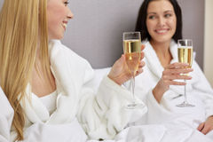 Happy women in bathrobes with champagne glasses. Holidays, celebration, people and drinks concept - two happy woman in bathrobes with champagne glasses at hotel royalty free stock photo