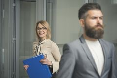 Happy woman with blurred man in foreground. Business woman in glasses hold file folder. Sexy secretary smile with office Stock Photography