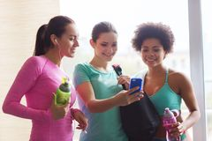 Happy women with bottles and smartphone in gym Stock Images