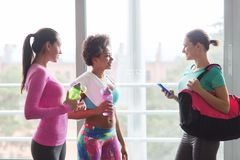 Happy women with bottles of water in gym Stock Photography