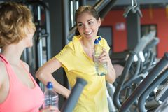 Happy women with bottles water talking in gym Stock Photography