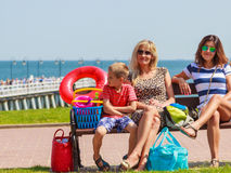 Happy women and boy kid resting on bench. Stock Photos