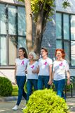 Happy women with breast cancer awareness ribbons holding hands and walking. Together royalty free stock images