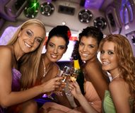 Happy women celebrating smiling. Happy women celebrating in limousine, smiling, looking at camera Stock Photo