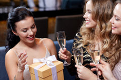 Happy women with champagne and gift at night club Stock Image