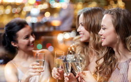 Happy women with champagne glasses at night club. Celebration, friends, bachelorette party and holidays concept - happy women with champagne glasses at night Royalty Free Stock Photos