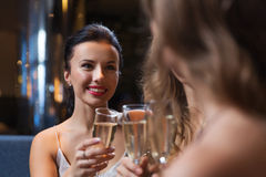 Happy women with champagne glasses at night club. Celebration, friends, bachelorette party and holidays concept - happy women with champagne glasses at night Royalty Free Stock Images