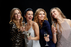 Happy women with champagne glasses over black Royalty Free Stock Photography