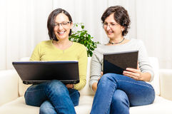 Happy women chat browsing home laptop Stock Images