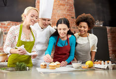 Happy women and chef cook baking in kitchen Royalty Free Stock Image