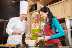 Happy women and chef cook baking in kitchen Stock Images