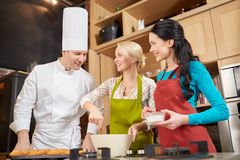 Happy women and chef cook baking in kitchen Stock Photos