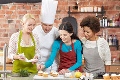Happy women and chef cook cooking in kitchen Stock Photography