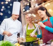 Happy women and chef cook cooking in kitchen Stock Images