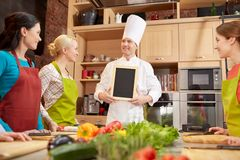Happy women and chef cook with menu in kitchen. Cooking class, culinary, food and people concept - happy women and chef cook with blank menu chalk board in stock photos