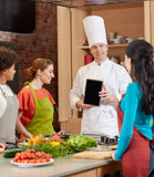 Happy women with chef and tablet pc in kitchen Royalty Free Stock Photography