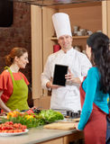 Happy women with chef and tablet pc in kitchen Royalty Free Stock Image