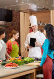 Happy women with chef and tablet pc in kitchen Stock Photo