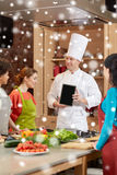 Happy women with chef and tablet pc in kitchen Stock Image
