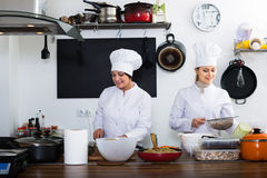 Happy women chefs cooking food at kitchen Stock Images