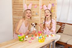 Happy woman with child paint easter eggs Stock Images